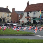 Newbald Green ahead of Jubilee Celebrations a row of Union jacks flying in the wind.